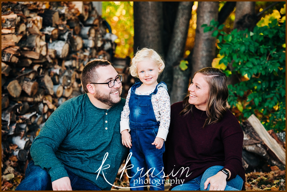 Photo of family including dad, toddler girl with blonde ringlets, and mom