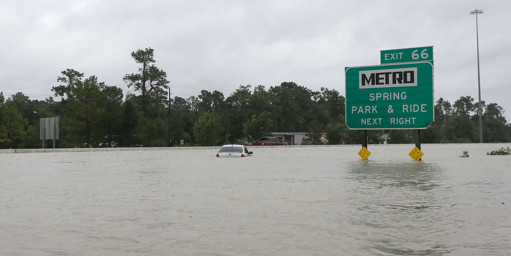 . A car sits along a flooded section of Interstate 45 as floodwaters from Tropical Storm Harvey rise Monday, Aug. 28, 2017, in Spring, Texas. (AP Photo/David J. Phillip)
