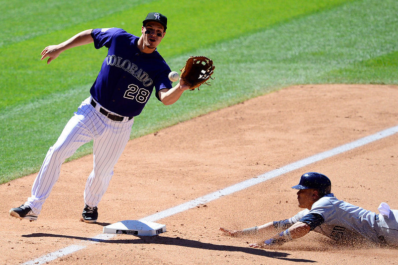 . San Diego Padres center fielder Alexi Amarista (5) slides into third safely with a steal as ,c28 makes a catch during the action in Denver. The Colorado Rockies hosted the San Diego Padres at Coors Field on Sunday, June 9, 2013. (Photo by AAron Ontiveroz/The Denver Post)