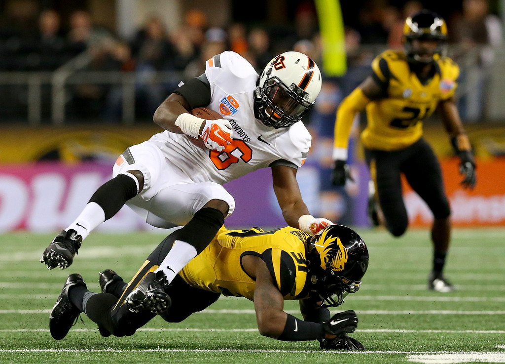 . ARLINGTON, TX - JANUARY 03:  Ashton Lampkin #6 of the Oklahoma State Cowboys is tackled by E.J. Gaines #31 of the Missouri Tigers in the second quarter during the AT&T Cotton Bowl on January 3, 2014 in Arlington, Texas.  (Photo by Ronald Martinez/Getty Images)