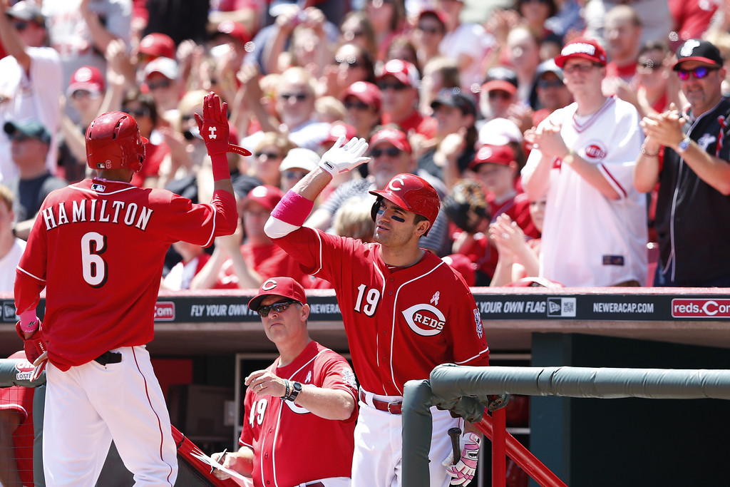 . Billy Hamilton #6 of the Cincinnati Reds is congratulated by Joey Votto #19 after scoring on a ground out by Skip Schumaker in the first inning of the game against the Colorado Rockies at Great American Ball Park on May 11, 2014 in Cincinnati, Ohio. (Photo by Joe Robbins/Getty Images)