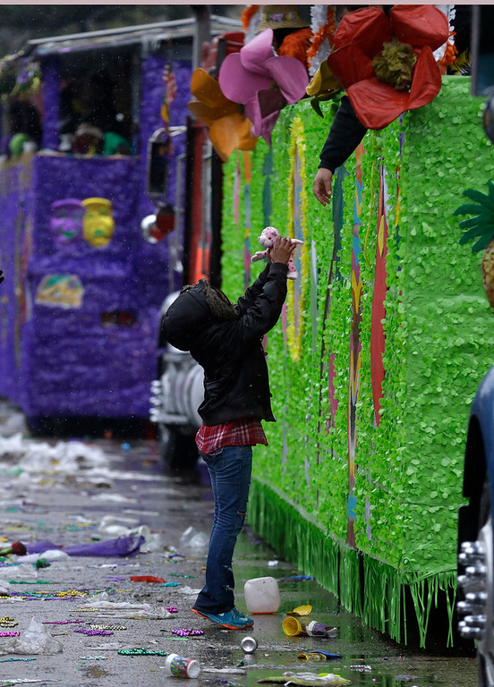 . A lone child reaches for a stuffed toy handed to him from a float rider during Mardi Gras in New Orleans, Tuesday, March 4, 2014. Rain and unusually cold temperatures kept most of the normally massive and festive crowds away.  (AP Photo/Gerald Herbert)