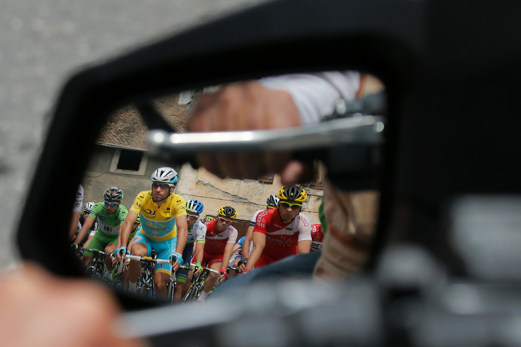 . Italy\'s Vincenzo Nibali, wearing the overall leader\'s yellow jersey, and the pack are reflected in the mirror of a motorcycle during the fifteenth stage of the Tour de France cycling race over 222 kilometers (137.9 miles) with start in Tallard and finish in Nimes, France, Sunday, July 20, 2014. (AP Photo/Christophe Ena)