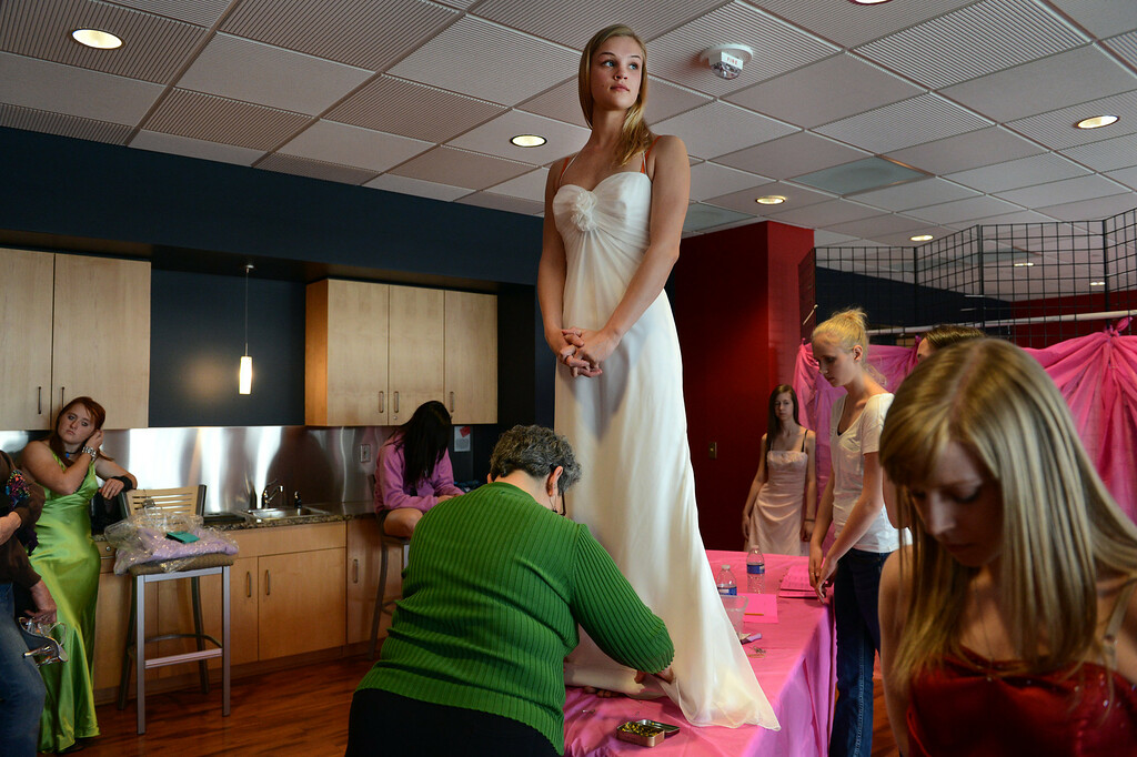 """. COMMERCE CITY, CO. - MARCH 16: Amanda Matheson, a junior at Grandview High School, has her dress altered by volunteer Diann Kissell during the Prom Dress Exchange Corp. event in Commerce City, CO March 16, 2013.  With a valid student ID and a suggested $10 donation, teenage girls could chose from 1,356 donated dresses that lined a long hallway at Dick�s Sporting Goods Park. Matheson said, \""""I almost feel like I\'m stealing. It\'s a great way not to spend a lot on prom.\"""" (Photo By Craig F. Walker/The Denver Post)"""