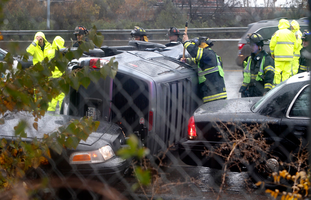 . Emergency crews work around a truck that rolled after striking a California Highway Patrol squad car along flooded Highway 87 in San Jose, Calif., Thursday afternoon, Dec. 11, 2014. (Karl Mondon/Bay Area News Group)