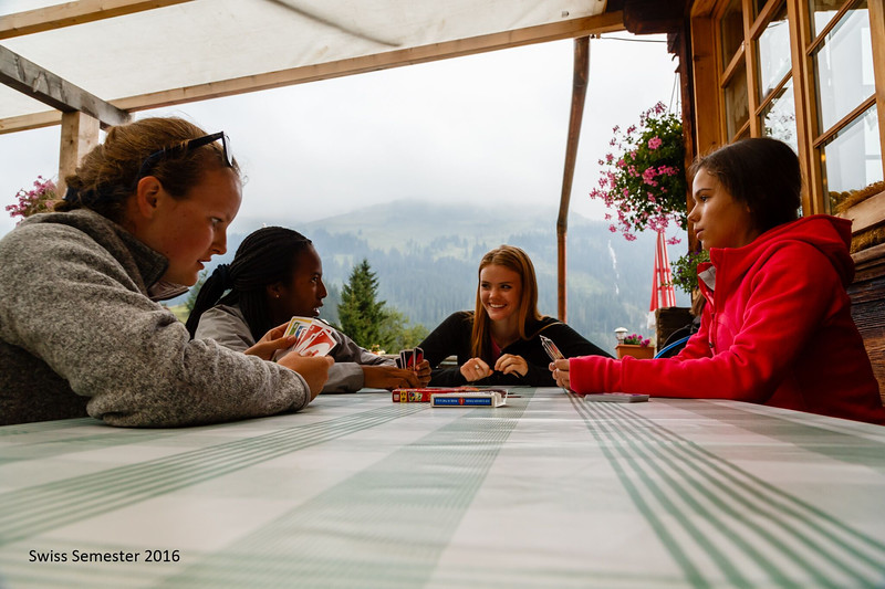 Caroline, Alyssa, Cara, and Whitney playing cards outside Naturfreunde in Gorderli