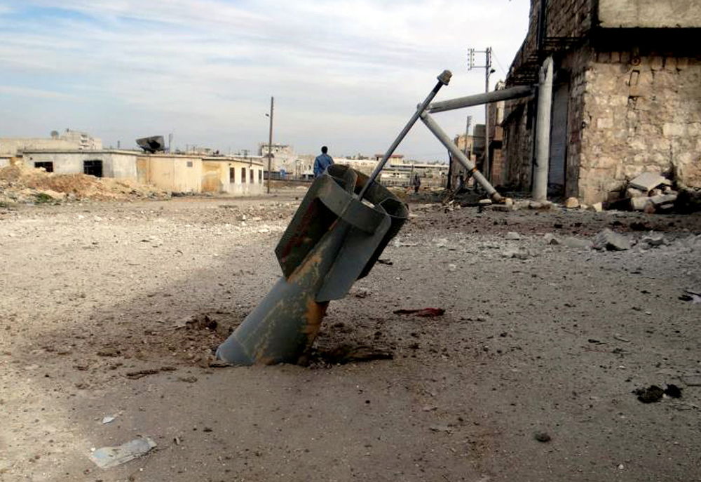 Description of . This citizen journalism image provided by Aleppo Media Center AMC which has been authenticated based on its contents and other AP reporting, shows an unexploded rocket from a Syrian warplane, in the neighborhood of Karam Alqasir, near Aleppo International Airport, in Aleppo, Syria, Thursday, Feb. 21, 2013. A car bomb near the Damascus headquarters of Syria's ruling party killed scores on Thursday, while a government airstrike on a rebel field hospital in southern Daraa left several dead, opposition activists and state media reported. (AP Photo/Aleppo Media Center AMC)