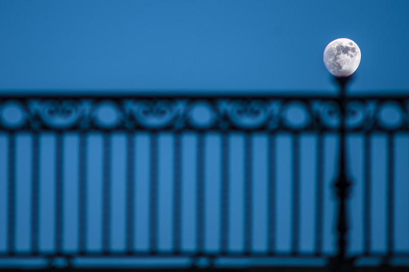 Waxing gibbous moon over the rail of the Triana bridge, Seville, Spain.