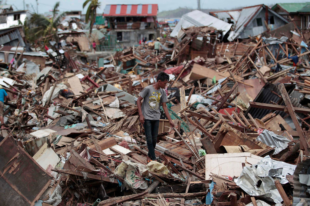 . A Filipino man walks along debris from damaged homes at typhoon-hit Tacloban city, Leyte province, central Philippines on Wednesday, Nov. 13, 2013. Typhoon Haiyan, one of the strongest storms on record, slammed into six central Philippine islands on Friday leaving a wide swath of destruction. (AP Photo/Aaron Favila)