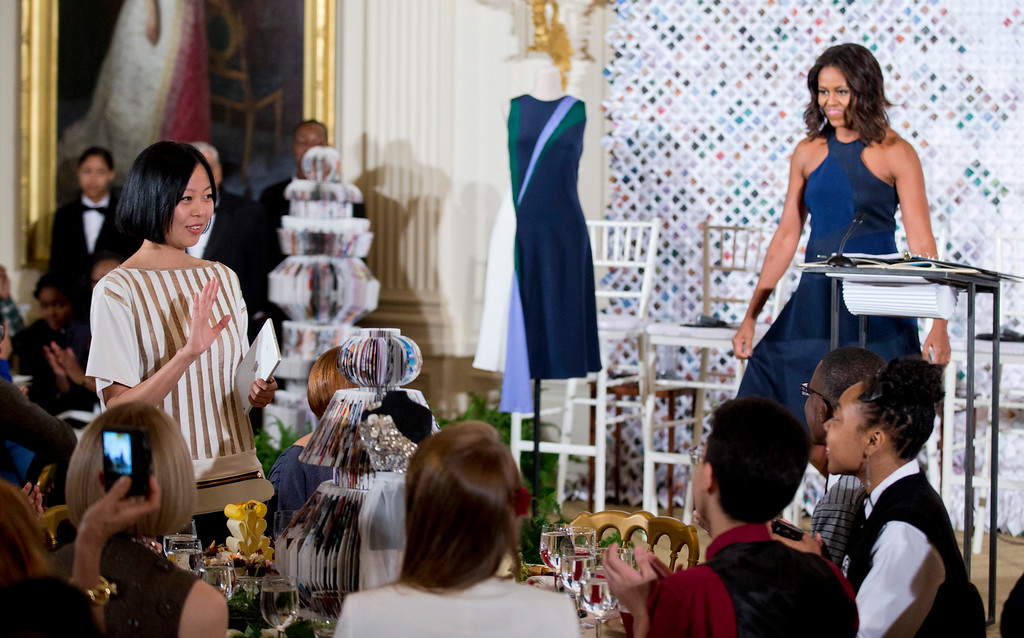 . First lady Michelle Obama introduces Chelsea Chen, left, who won a design competition, Wednesday, Oct. 8, 2014, during the Fashion Education Workshop at the White House in Washington. Chelsea Chen designed the dress shown on a mannequin.  (AP Photo/Manuel Balce Ceneta)