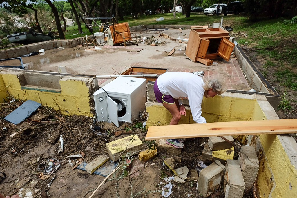 . Janie Bell helps her neighbors search for possessions after their vacation home was destroyed in a flash flood along the Blanco River, Monday, May 25, 2015, in Wimberley, Texas. Several people were reported missing in flash flooding from a line of storms that stretched from the Gulf of Mexico to the Great Lakes. (Rodolfo Gonzalez/Austin American-Statesman via AP)