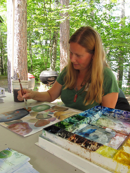 It is fitting that this artist is painting a water scene with watercolor paints!