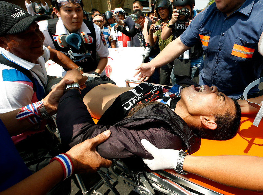 . A gunshot injured Thai anti-government protester is carried to a hospital during clashes with policemen at a protest site in Bangkok, Thailand, 18 February 2014.  EPA/RUNGROJ YONGRIT
