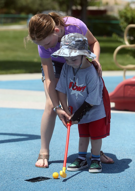 . Matthew Ouimet, 3, plays golf as his sister Molly, 11, assists at Markley Creek Park in Antioch, Calif., on Friday, May 23, 2014. (Jane Tyska/Bay Area News Group)