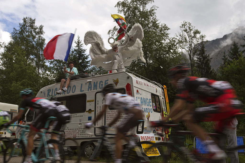 . Disguised supporters sit on the roof of a camper van cheer riders during the 172.5 km eighteenth stage of the 100th edition of the Tour de France cycling race on July 18, 2013 between Gap and Alpe-d\'Huez, French Alps. JOEL SAGET/AFP/Getty Images