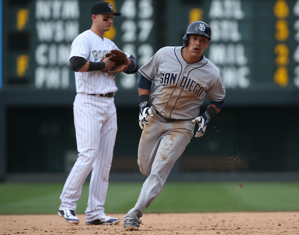 . San Diego Padres\' Everth Cabrera, front, circles the bases after hitting a two-run home run as Colorado Rockies shortstop Troy Tulowitzki looks on in the ninth inning of the Rockies\' 8-6 victory in 10 innings of a baseball game in Denver on Sunday, May 18, 2014. (AP Photo/David Zalubowski)