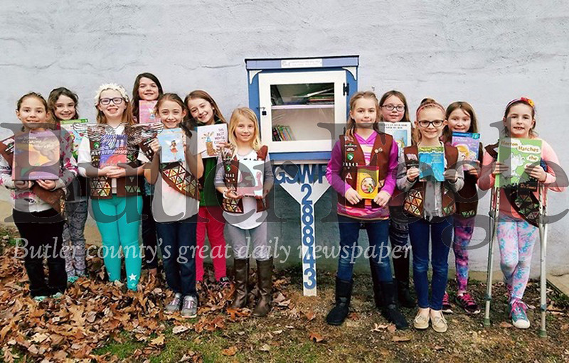 Girl Scouts from Troop 28843 stand next to the Little Free Library they built in the Connoquenessing Park.