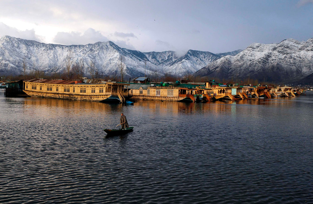 Description of . A Kashmiri man rows his boat in the waters of the Dal Lake on a cold winter evening in Srinagar February 5, 2013. REUTERS/Danish Ismail