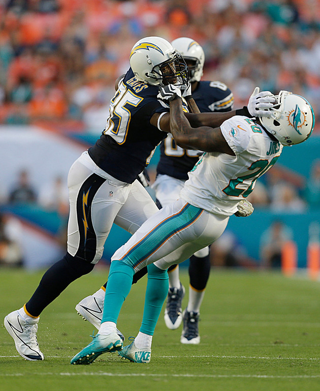 . Miami Dolphins free safety Reshad Jones (20) attempts to bring down San Diego Chargers tight end Antonio Gates (85) during the first half of an NFL football game, Sunday, Nov. 17, 2013, in Miami Gardens, Fla. (AP Photo/Wilfredo Lee)