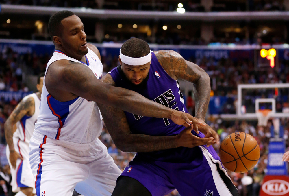 . Sacramento Kings center DeMarcus Cousins, right, loses the ball as he is fouled by Los Angeles Clippers forward Glen Davis, left, during the second half of an NBA basketball game in Los Angeles, Saturday, April 12, 2014. The Clippers won 117-101. (AP Photo/Danny Moloshok)
