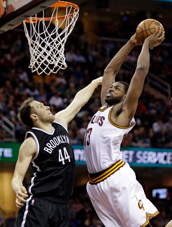 . Cleveland Cavaliers\' Tristan Thompson, right, dunks against Brooklyn Nets\' Bojan Bogdanovic, from Croatia, in the second half of an NBA basketball game, Friday, Dec. 23, 2016, in Cleveland. (AP Photo/Tony Dejak)