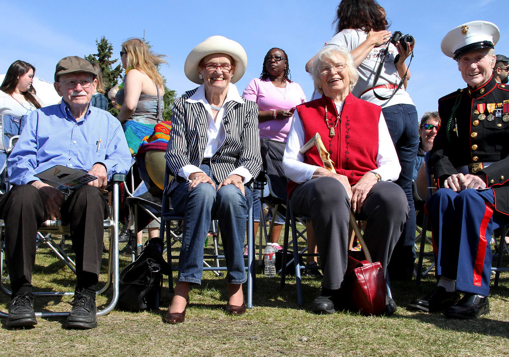 . Four former marshals of the Alaska Pride Parade, who led the Alaska Pride March in downtown Anchorage, are seated on Saturday, June 15, 2013. From left are Fred Hillman, who was the 2002 marshal; Katie Hurley and Arliss Sturgulewski, who were co-marshals in 2001, and Mike Madill, who was the marshal in 2005 and is seen wearing his uniform from World War II. Instead of  parade, a unity march was held from downtown to the Alaska Pride Festival on the Delaney Park Strip. (AP Photo/Mark Thiessen)