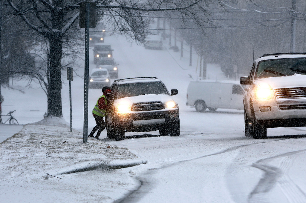 . Francios Bigand helps push a car as it attempts to climb a hill on Boylan Avenue during a winter storm Wednesday Feb. 12, 2014, in Raleigh, N.C. (AP Photo/The News & Observer, Travis Long)