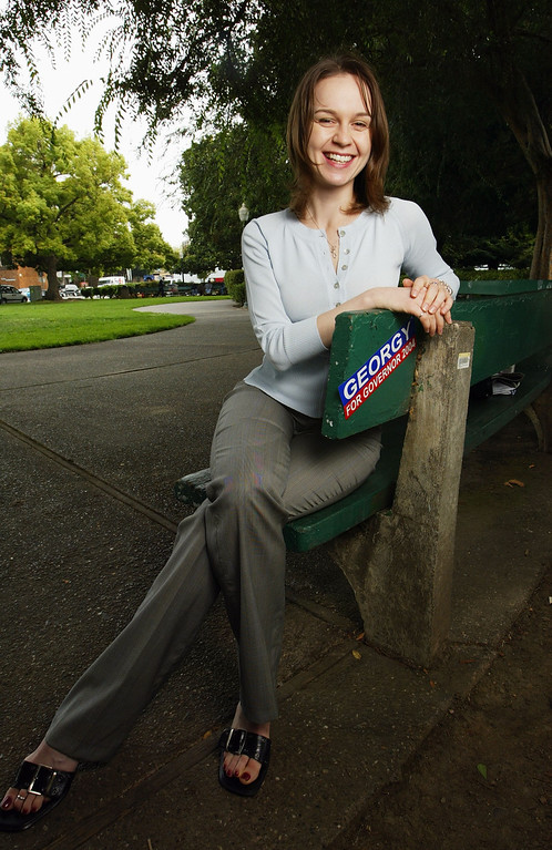 """. PALO ALTO, CA - JULY 29:  Twenty six-year-old Georgina \""""Georgy\"""" Russell, a potential candidate for California Governor, sits on a bench July 29, 2003 in Palo Alto, California. Russell, a computer programmer from Mountain View, California, is one of many Californians who are considering making a run for Governor\'s office since the recall election of Governor Gray Davis was made official. Russell has tackled popular issues and has a Web site where supporters can buy thong underwear, boxer shorts and other merchandise labeled \""""Georgy for Governor.\""""  (Photo by Justin Sullivan/Getty Images)"""