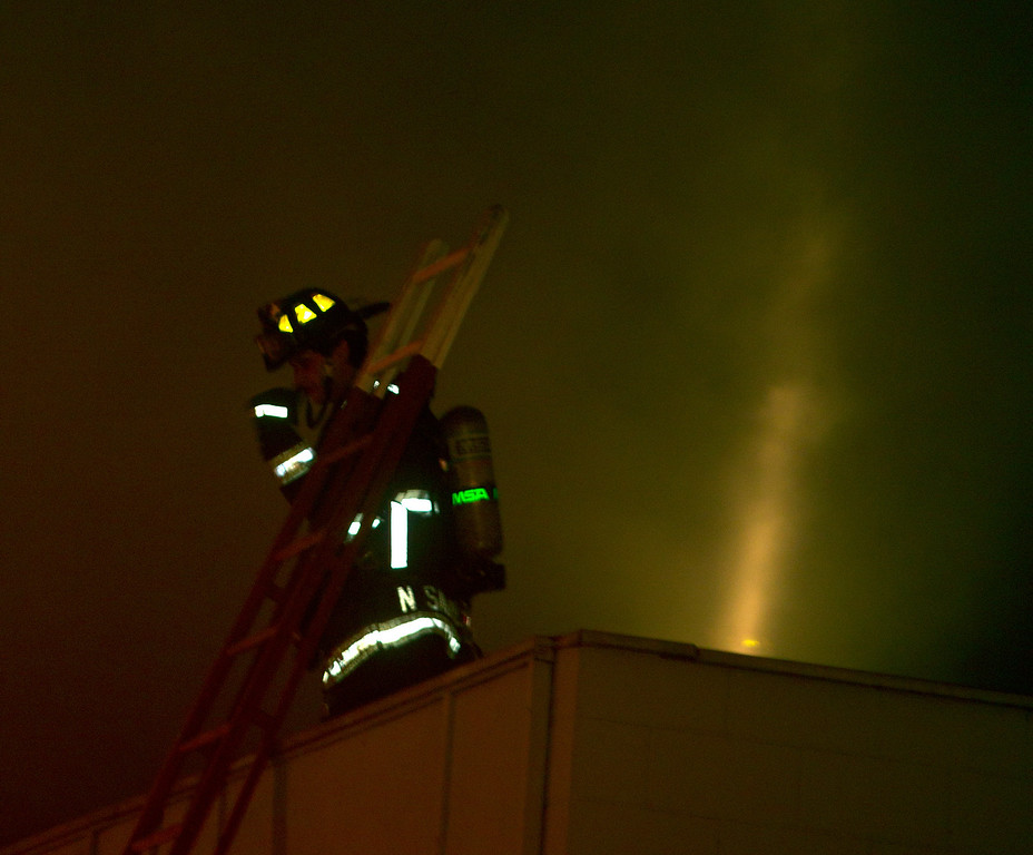 . A firefighter pauses atop the roof of an adjacent building while battling the flames from a fire inside a vacant, wood-framed house on Harrison Street near 7th Street, Wednesday, Jan. 23, 2013 in Oakland, Calif. The building, which fire investigators said was built in 1896, caught fire when squatters inside it tried to cook food over an open flame. (D. Ross Cameron/Staff)