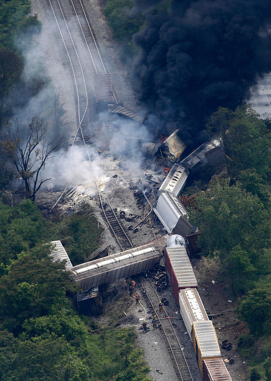 . A fire burns at the site of a CSX freight train derailment, Tuesday, May 28, 2013, in White Marsh, Md., where fire officials say the train crashed into a trash truck, causing an explosion that rattled homes at least a half-mile away and collapsed nearby buildings, setting them on fire. (AP Photo/Patrick Semansky)