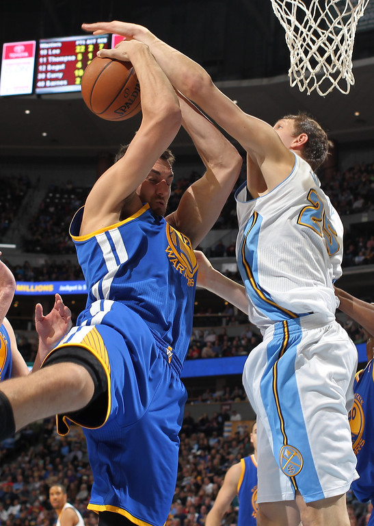 . Golden State Warriors center Andrew Bogut, left, of Australia, battles for control of a reobund with Denver Nuggets center Timofey Mozgov, of Russia, in the fourth quarter of the Warriors\' 89-81 victory in an NBA basketball game in Denver on Monday, Dec. 23, 2013. (AP Photo/David Zalubowski)