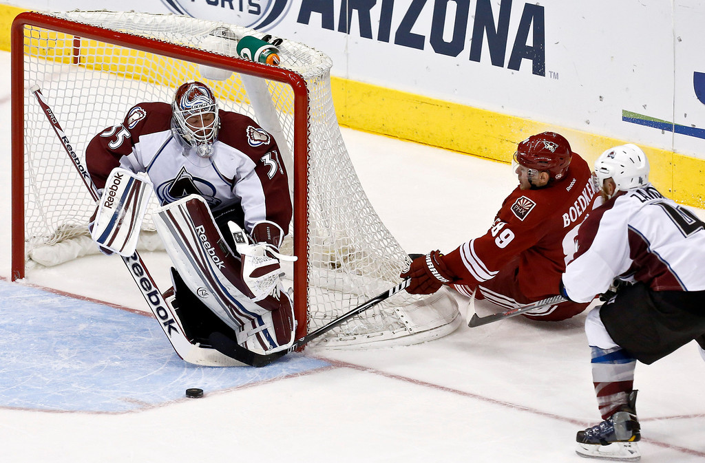 . Colorado Avalanche\'s Jean-Sebastien Giguere (35) makes a save on a shot by Phoenix Coyotes\' Mikkel Boedker (89), of Denmark, as the Avalanche\'s Greg Zanon, right, defends during the third period in an NHL hockey game, on Friday, April 26, 2013, in Glendale, Ariz.  The Avalanche defeated the Coyotes 5-4 in a shootout. (AP Photo/Ross D. Franklin)