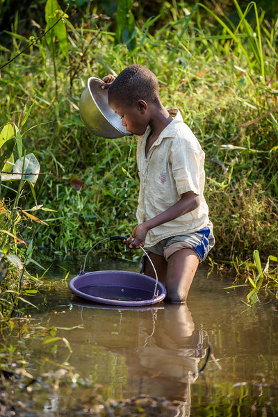 """Grace Mukoma, 10 yr-old boy, pauses from collecting water from a swamp near his home in Kananga, Central Kasai Province, DRC, to take a long drink of the polluted water.  Water Every day, Grace follows a winding, dirt path behind his house for about a mile. It leads downhill to a muddy pond. The water is brown and has a filmy covering on it. Grace rolls up his pants and wades in with a small, purple bucket which he fills up with a smaller, stainless steel bowl.  When the bucket is full, Grace struggles to carry it uphill eventually putting it on his head. He doesn't spill a drop.    """"I get water from the stream as many as 4 or 5 times a day. The walk takes around 1 hour both ways. The water is not good. Sometimes I get sick from it.""""  Background Grace lives with his mom, Mbombo Elize, sister Harriet, 7, and an extended family of relatives, including his grandmother, Kapinga Godelive, 66.  Mbombo has had 4 children, the first when she was 15. 2 died during the time they had to run away because of the war. Now it's just Grace and his sister Harriet, 7.  They live in the Kasai Centrale province in a place called Katoka. It's a rural community. Grace and his family had to run when war broke out in the DRC.  His father was killed. His mother and her 4 children ran about 2 kilometers down the road from his house towards the Lualua River. They hid there for about 3 months. Unfortunately, because of a lack of food and disease, Grace's brother and a sister died. After about 3 months Grace and his family hesitantly made their way back to their house. It had been burnt and was empty. They've struggled ever since.    Here's a look at Grace's life today:  Home Life  """"Early in the morning I sweep the compound. Then I wash and if there is food I eat. Then I join my friends at the CFS."""" """"Sometimes they send me on other errands. If they need something, they send me.""""  Food Grace's family doesn't have enough food. On any given day they may or may not eat. When they do eat, it's once """