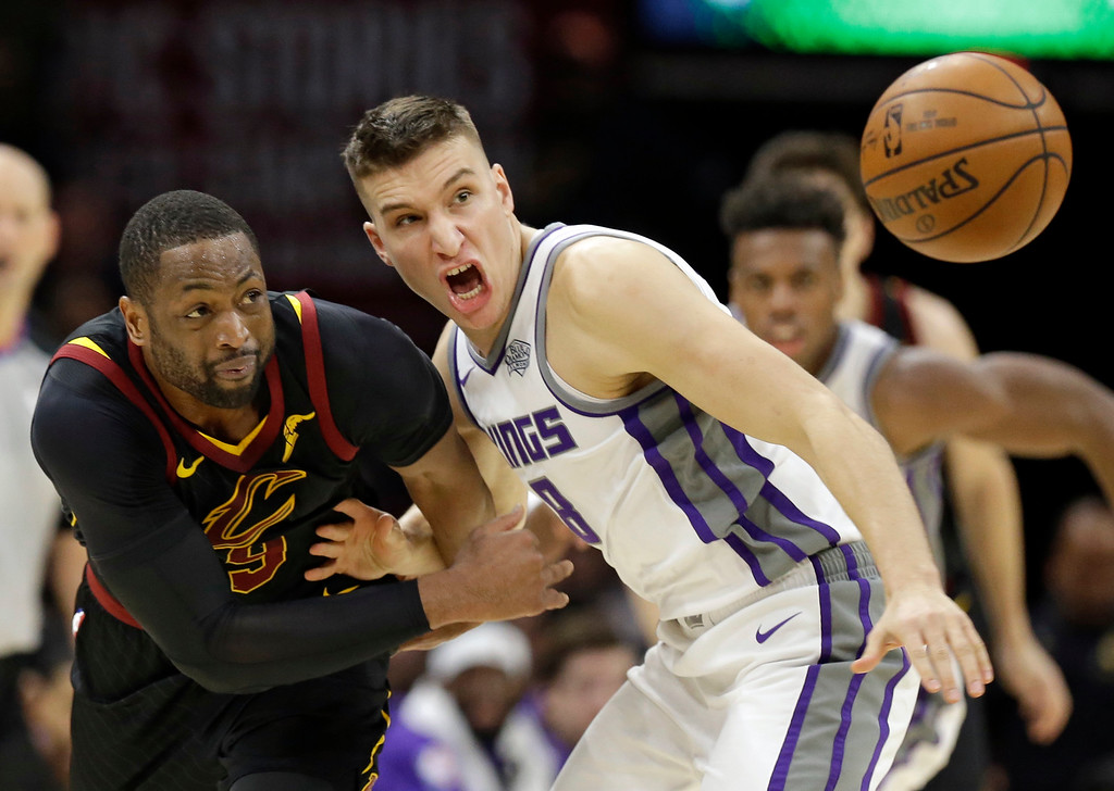 . Cleveland Cavaliers\' Dwyane Wade, left, and Sacramento Kings\' Bogdan Bogdanovic, from Serbia, battle for a loose ball in the second half of an NBA basketball game, Wednesday, Dec. 6, 2017, in Cleveland. The Cavaliers won 101-95. (AP Photo/Tony Dejak)