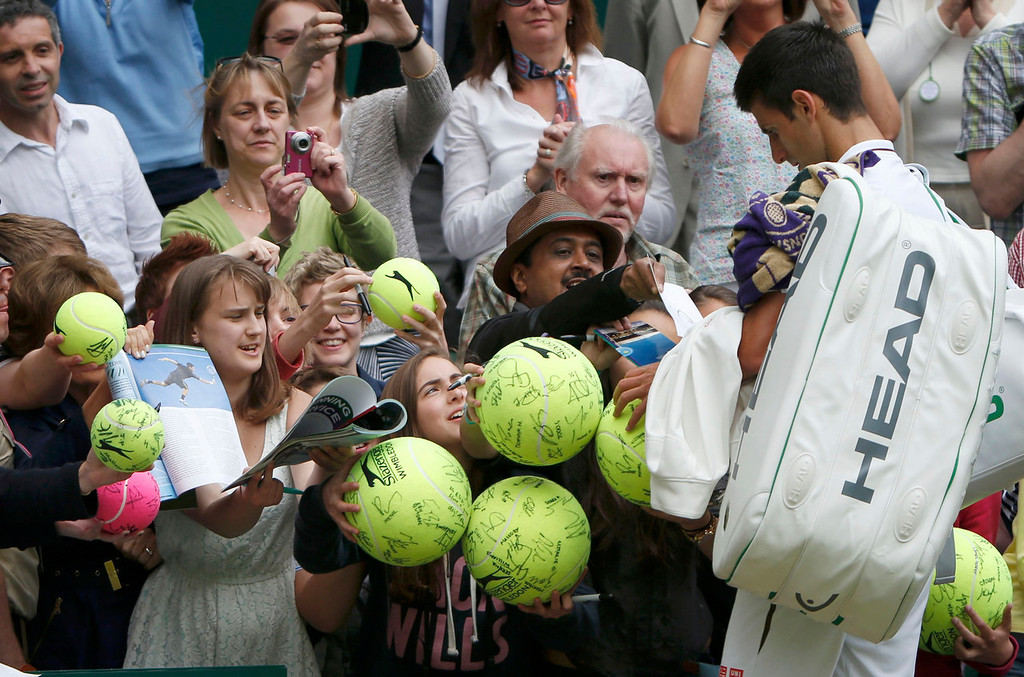 . Novak Djokovic of Serbia signs autographs after defeating Florian Mayer of Germany in their men\'s singles tennis match at the Wimbledon Tennis Championships, in London June 25, 2013.  REUTERS/Eddie Keogh