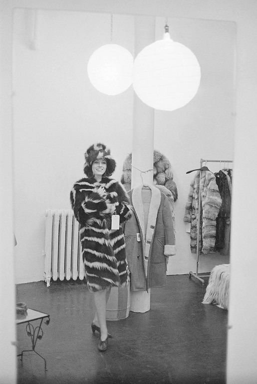 ". Jacqueline Sigesmund of Winnipeg, Canada trys on a black and white natural skunk coat with a matching hat at the fun fur shop, ""Mr. A.\"" in New York\'s Greenwich Village on Jan. 19, 1966. (AP Photo)"