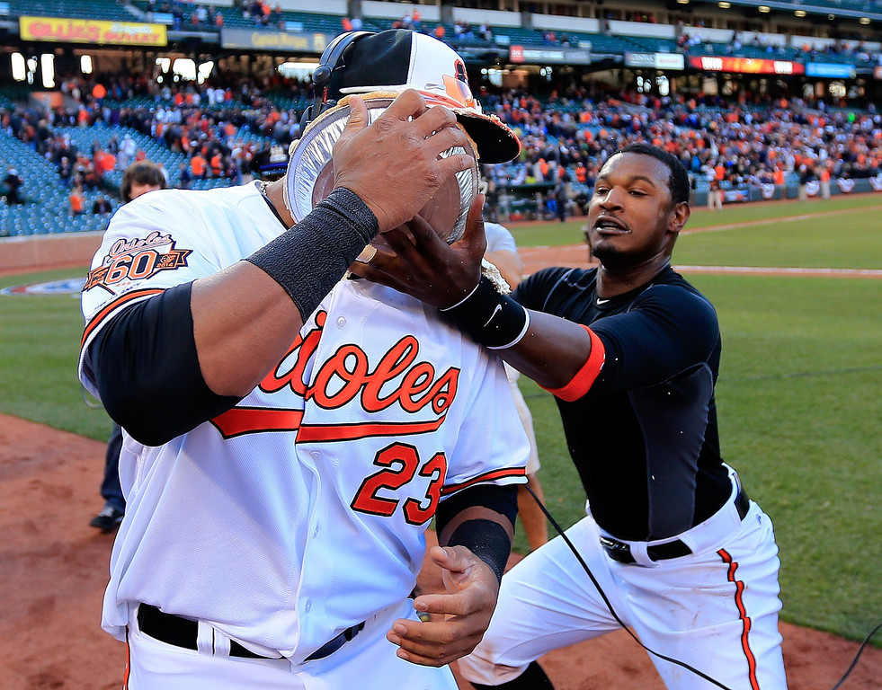 . Nelson Cruz #23 of the Baltimore Orioles gets hit with a pie in the face from teammate Adam Jones #10 after the Orioles 2-1 win over the Boston Red Sox during Opening Day at Oriole Park at Camden Yards on March 31, 2014 in Baltimore, Maryland.  (Photo by Rob Carr/Getty Images)