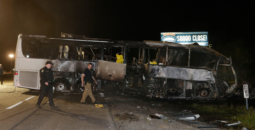 . A pair of California Highway Patrol Officers walk past the burned out tour bus where at least nine people died in a fiery crash between a tour bus and a FedEx truck on Interstate 5 Thursday, April 10, 2014, in Orland, Calif. (AP Photo/Rich Pedroncelli)