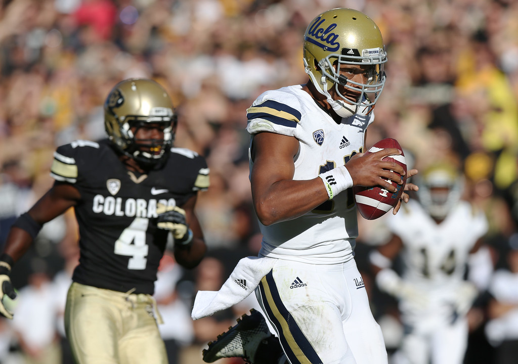 . UCLA quarterback Brett Hundley, front, runs in for the winning touchdown as Colorado defensive back Chidobe Awuzie covers in the second overtime of UCLA\' 40-37 victory in double overtime in an NCAA football game in Boulder, Colo., on Saturday, Oct. 25, 2014. (AP Photo/David Zalubowski)