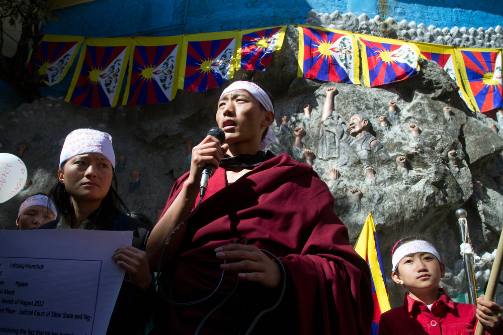 Description of . An exiled Tibetan Buddhist monk speaks in front of a sculpted wall showing a Tibetan uprising during a protest gathering in solidarity with the Tibetan immolators in Dharmsala, India, Tuesday, Feb. 12, 2013. Tibetans were protesting the recent death sentence of Tibetan Lobsang Kunchok, accused by the Chinese government of inciting the Tibetans to immolate themselves. (AP Photo/ Ashwini Bhatia)