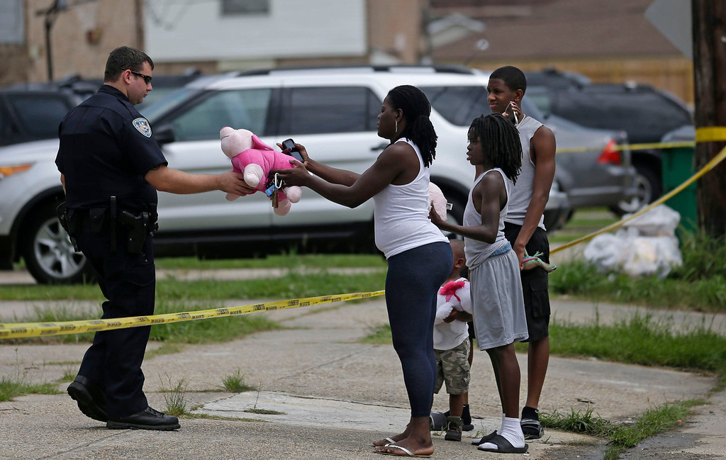 . Joanna Jones hands a teddy bear to a Jefferson Parish Sheriff, to place at a makeshift memorial inside a crime scene where the body of missing 6-year-old Ahlittia North was found in Harvey, La., Tuesday, July 16, 2013. Lisa North, the mother of  Ahlittia, says Jefferson Parish authorities have found the body of her daughter in a Harvey trash bin. Ahlittia disappeared from her apartment late Friday night or early Saturday morning. North\'s husband Albert Hill said they were told the body was found in a trash bin not far from their apartment. (AP Photo/Gerald Herbert)