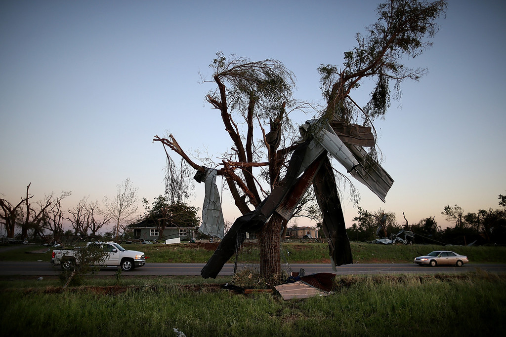 . TORNADO PROJECT EL RENO, OK - JUNE 01:  Metal siding hangs from a tree after a series of tornadoes ripped through the area a day earlier on June 1, 2013 in El Reno, Oklahoma. A series of tornadoes ripped through the area on Friday evening killing at least nine people, injuring many others and destroying homes and buildings.  (Photo by Justin Sullivan/Getty Images)
