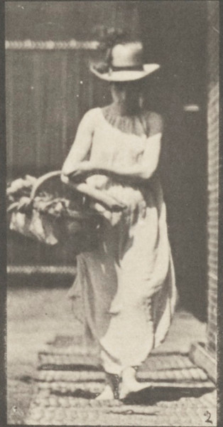 Semi-nude woman placing a basket on the ground and turning