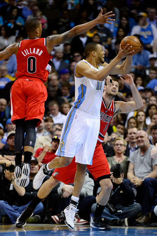 . DENVER, CO - APRIL 14: Anthony Randolph (15) of the Denver Nuggets drives against Damian Lillard (0) of the Joel Freeland (19) of the Portland Trail Blazers during the second half of action. The Denver Nuggets defeat the Portland Trail Blazers 118-109 at the Pepsi Center. (Photo by AAron Ontiveroz/The Denver Post)