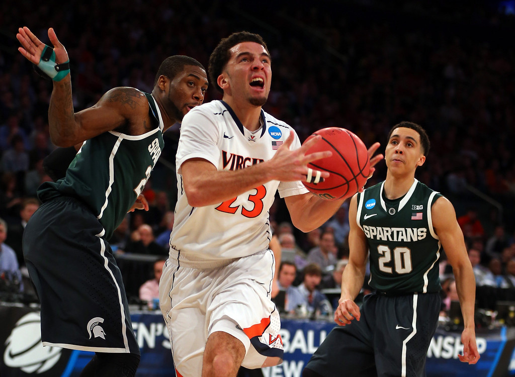 . London Perrantes #23 of the Virginia Cavaliers drives the ball against Branden Dawson #22 and Travis Trice #20 of the Michigan State Spartans during the regional semifinal of the 2014 NCAA Men\'s Basketball Tournament at Madison Square Garden on March 28, 2014 in New York City.  (Photo by Elsa/Getty Images)