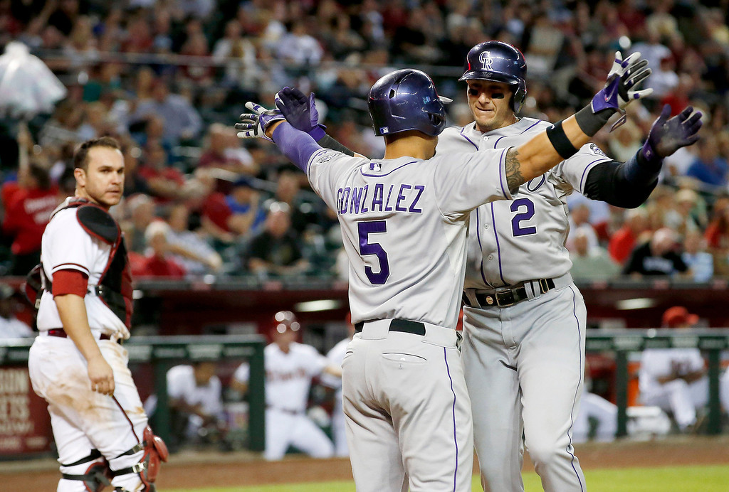 . Colorado Rockies\' Troy Tulowitzki (2) celebrates his two-run home run against the Arizona Diamondbacks with teammate Carlos Gonzalez (5) as Diamondbacks\' Miguel Montero, left, stands near during the sixth inning of a baseball game on Tuesday, April 29, 2014, in Phoenix. (AP Photo/Ross D. Franklin)
