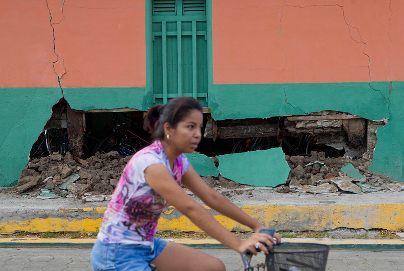 . A girl passes by in a bicycle, in front a home damaged by an earthquake in Nagarote, Nicaragua, Friday, April 11, 2014. Nicaragua\'s President Daniel Ortega declared red alert Friday after an earthquake of 6.2 magnitude on the Richter scale that shook the country on Thursday and left one dead, hundreds of houses damaged and thousands of people affected . (AP Photo/Esteban Felix)