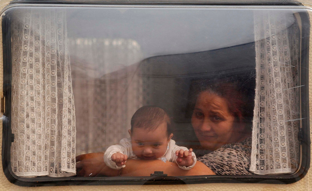 """. A Roma woman and her baby, referred to as \""""gens du voyage\"""" are seen though the window of their caravan at a camp in Strasbourg, April 8, 2013. REUTERS/Vincent Kessler"""