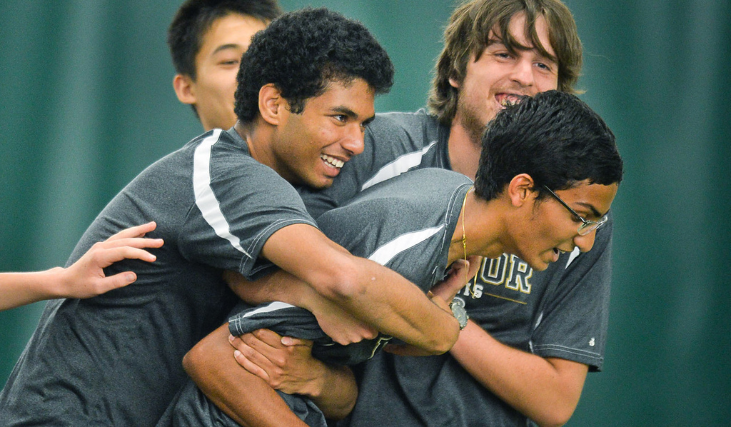 . Nikhil Gupta of East Ridge, right, is mobbed by teammates after he beat Abraham Alex of Mounds View in the State Class AA Boys\' Tennis Tournament team quarterfinals at the Baseline Tennis Center at the University of Minnesota in Minneapolis on Tuesday, June 3, 2014. East Ridge knocked the top-seeded Mustangs out of the team tournament.  (Pioneer Press: Ben Garvin)