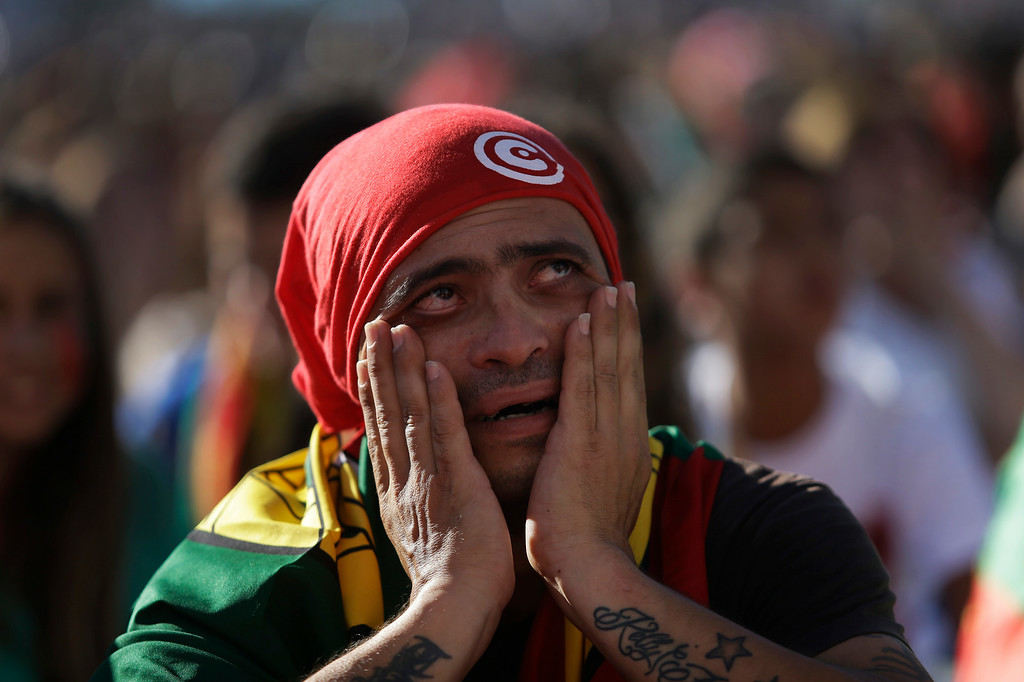 . A Portuguese supporter reacts as he and others watch the World Cup soccer match between Portugal and Ghana being played in Brazil, on a giant screen in Lisbon, Thursday, June 26, 2014. Despite Portugal winning the match 2-1 it failed to get to the second round due to the goal difference with the U.S. team. (AP Photo/Francisco Seco)